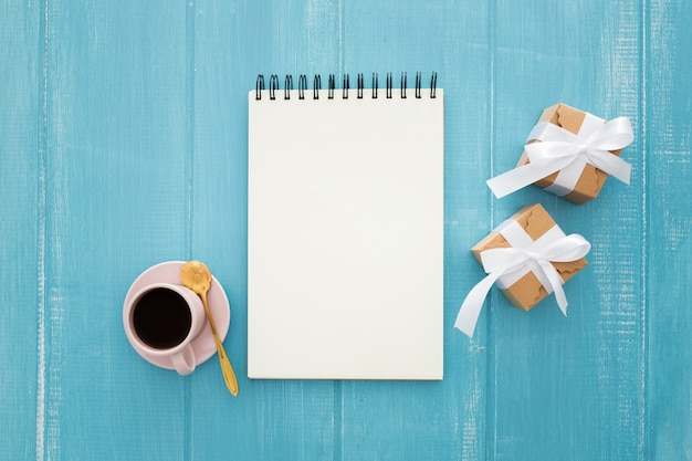 Notizbuch und geschenkboxen mit kaffee auf einem blauen hölzernen Kostenlose Fotos