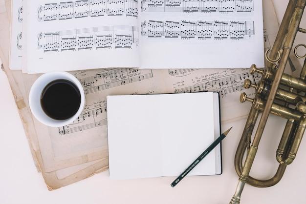 Notizbuch und kaffee nahe noten und trompete Kostenlose Fotos
