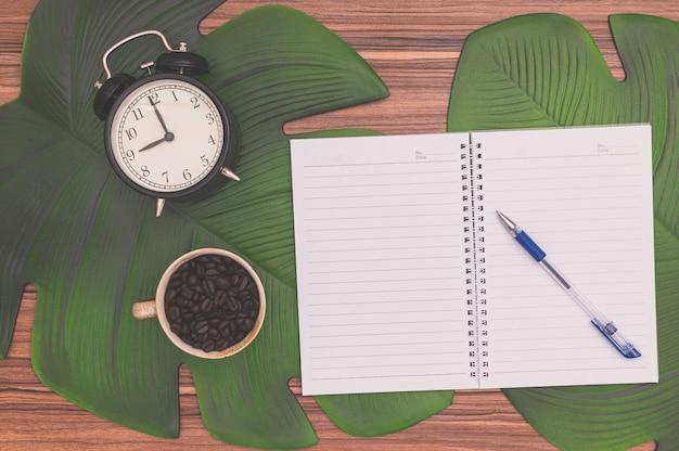 Notizbuch und kaffeetasse auf dem schreibtisch Premium Fotos
