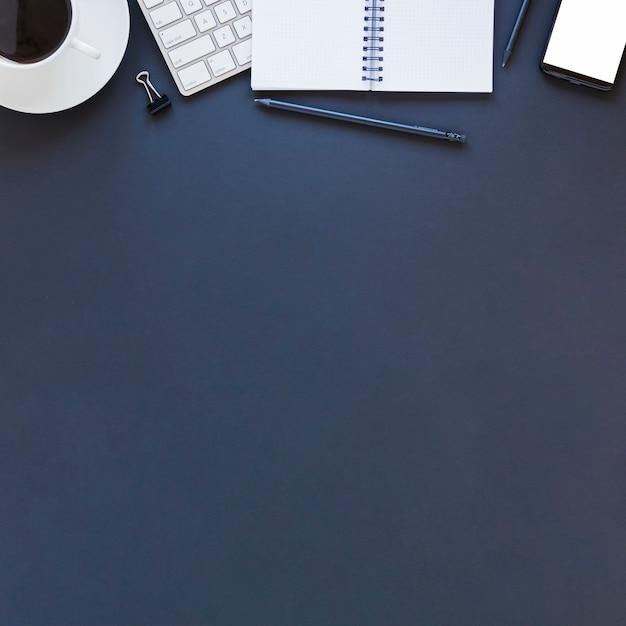 Notizbuch und kaffeetasse der elektronischen geräte auf dunkelblauer tabelle Kostenlose Fotos