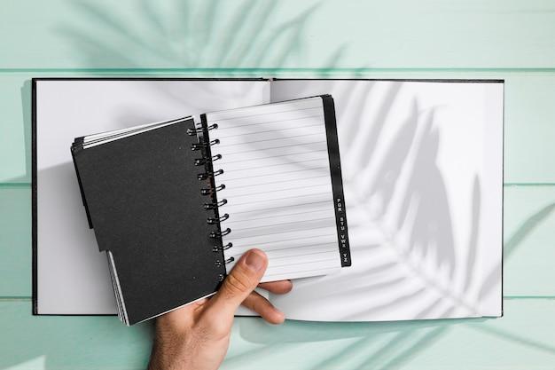 Notizbuch- und kopienraum mit schatten von blättern Kostenlose Fotos