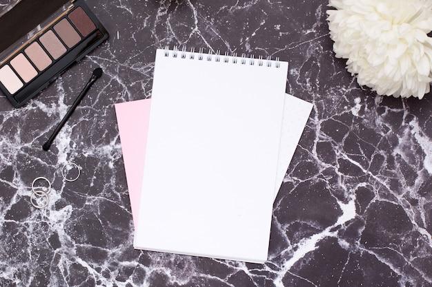 Notizbuch und kosmetik der frauen auf schwarzer marmortabelle Premium Fotos