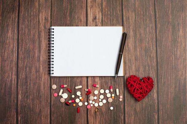 Notizbuch und stift mit rotem herzen und pillen auf holz Premium Fotos