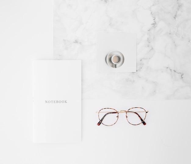 Notizbuchtext auf papier; kaffeetasse und brille auf weißem beschaffenheitshintergrund Kostenlose Fotos