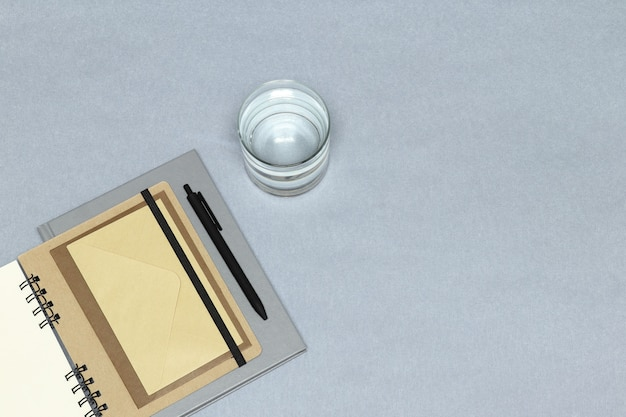 Notizbücher, schwarzer stift, umschläge, glas wasser auf dem grauen hintergrund Premium Fotos