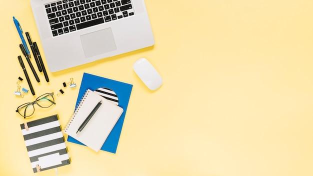 Notizbücher und laptop mit schreibwaren auf farbigem hintergrund Kostenlose Fotos