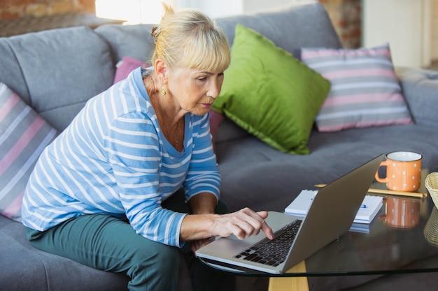 Notizen während des unterrichts machen. ältere frau, die zu hause studiert und online-kurse erhält Kostenlose Fotos