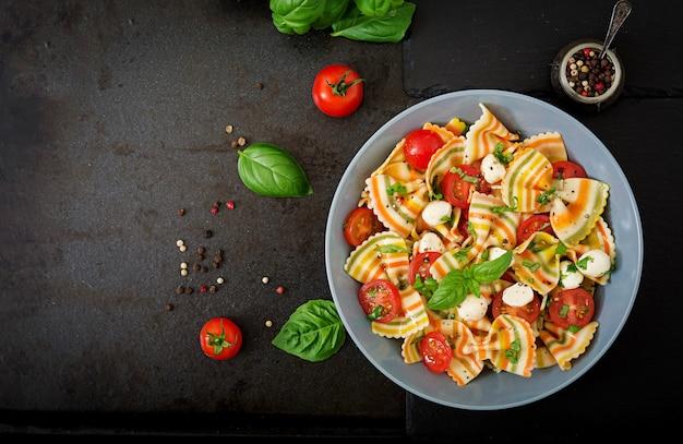 Nudelfarbener farfalle-salat mit tomaten, mozzarella und basilikum. Kostenlose Fotos