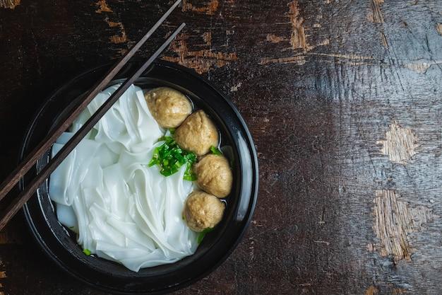 Nudeln mit fleischklöschen auf einem holztisch Premium Fotos