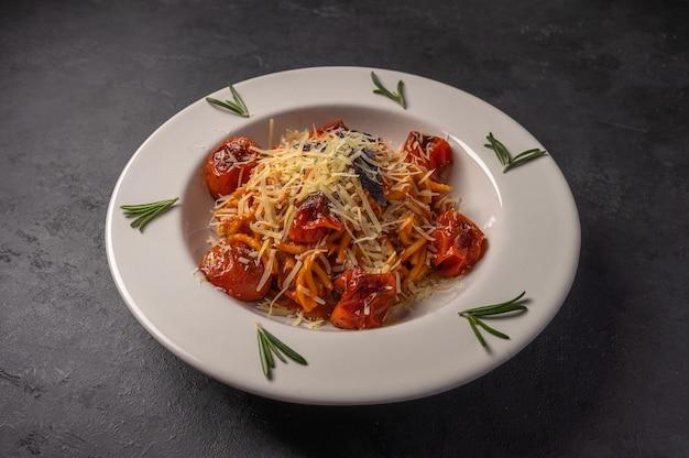 Nudeln mit kirschtomaten, käse und rosmarin serviert auf teller auf dunklem strukturiertem hintergrund, kopie Premium Fotos