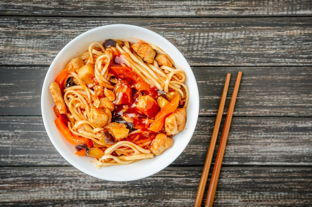 Nudeln udon in der süßen und sauren soße und in den essstäbchen auf holztisch Premium Fotos
