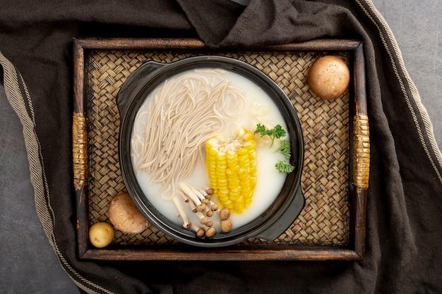 Nudelsuppe mit mais in einer schwarzen schüssel auf einem holztisch Kostenlose Fotos