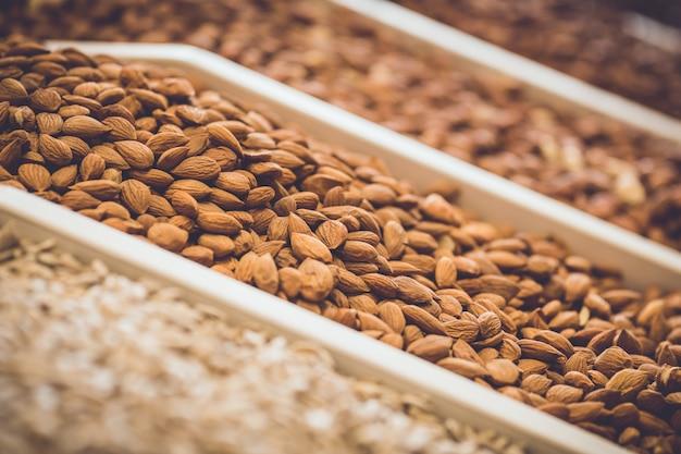 Nüsse in den regalen. verschiedene sorten von erdnüssen und mandeln. Premium Fotos