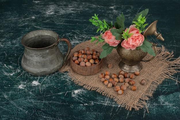 Nüsse mit blumenvase auf marmor. Kostenlose Fotos