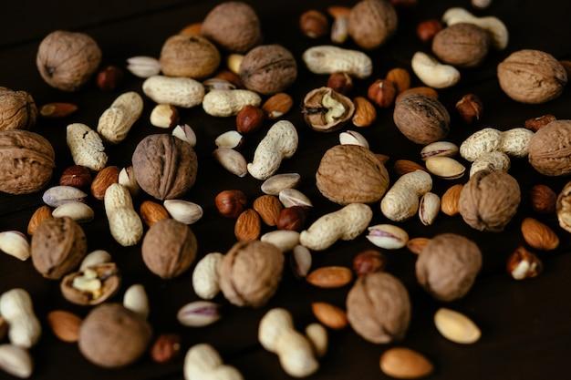 Nüsse. pistazie, walnuss, haselnuss und erdnuss. mischnüsse auf schwarzem hintergrund Kostenlose Fotos