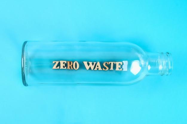 Null-abfall-konzept. leere glasflasche für das einkaufen und die lagerung des nullabfalls auf blauem hintergrund Premium Fotos