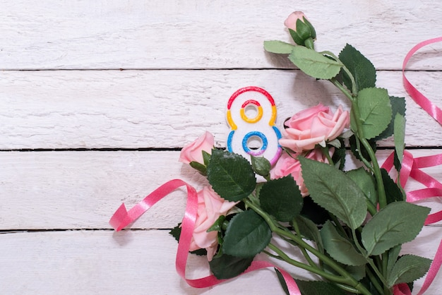 Nummer acht als symbol eines feiertags 8. märz und rosa rosen auf holztisch. grußkarte mit blumen für internationalen frauentag. speicherplatz kopieren Premium Fotos