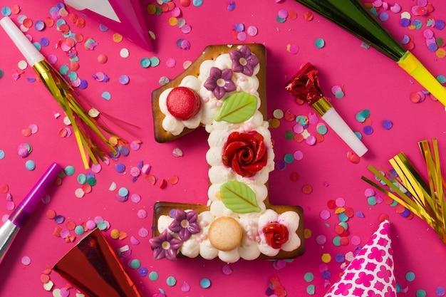 Nummer eins kuchen mit blumen und kekse auf rosa oberfläche verziert. Premium Fotos