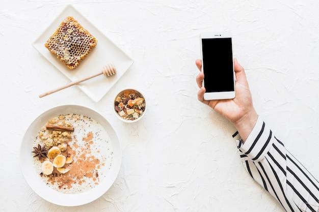 Oatmeals; dryfruits und bienenwabe auf tabelle mit mobiltelefon in den händen Kostenlose Fotos
