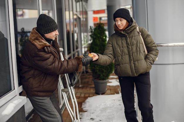 Obdachlose in einer winterstadt. mann, der um essen bittet. Kostenlose Fotos