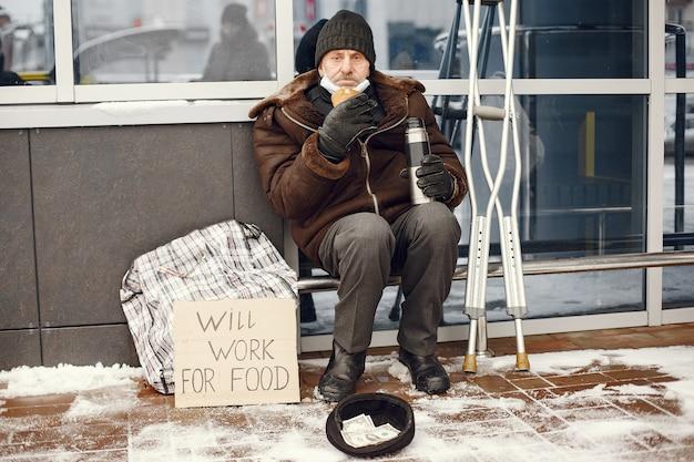 Obdachlose sitzen in der nähe des gebäudes. Kostenlose Fotos