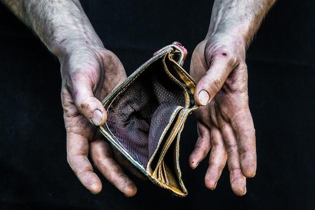 Obdachloser armer mann der schmutzigen hände mit leerer geldbörse in der modernen kapitalismusgesellschaft Premium Fotos