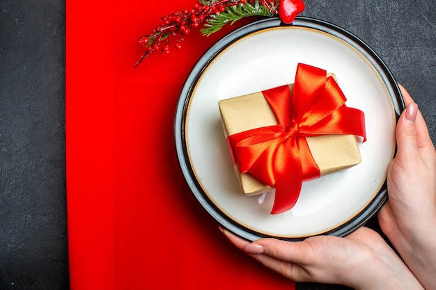 Oben ansicht des nationalen weihnachtsmahlzeithintergrundes mit hand, die leere teller mit bogenförmigem rotem band und tannenzweigen auf einer roten serviette auf schwarzem tisch hält Kostenlose Fotos