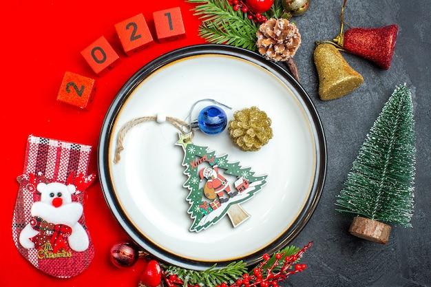 Oben ansicht des neujahrshintergrunds mit esstischdekorationszubehör tannenzweigen und zahlenweihnachtssocke auf einer roten serviette neben weihnachtsbaum auf einem schwarzen tisch Kostenlose Fotos
