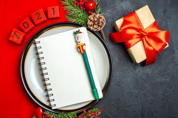 Oben ansicht des neujahrshintergrunds mit spiralheft auf tellerdekorationszubehör tannenzweigen und zahlen auf einer roten serviette und geschenk mit rotem band auf einem schwarzen tisch Kostenlose Fotos
