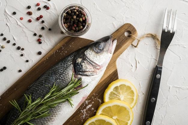 Oben ansicht fisch mit kräutern und zitrone Kostenlose Fotos