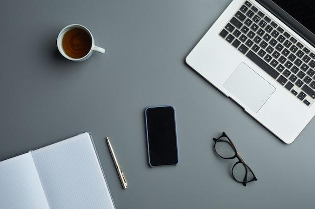 Oben ansicht flache lage von laptop und geschäftszubehör auf grauem arbeitsplatzhintergrund, Premium Fotos