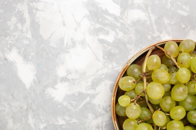 Oben nahansicht frische grüne trauben saftig milde süße früchte auf weißen schreibtischfrüchten frischen milden saft wein Kostenlose Fotos