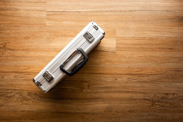 Oben von metall aktentasche (box) auf holzboden hintergrund. werkzeug und sicherheitskonzepte ideen Premium Fotos