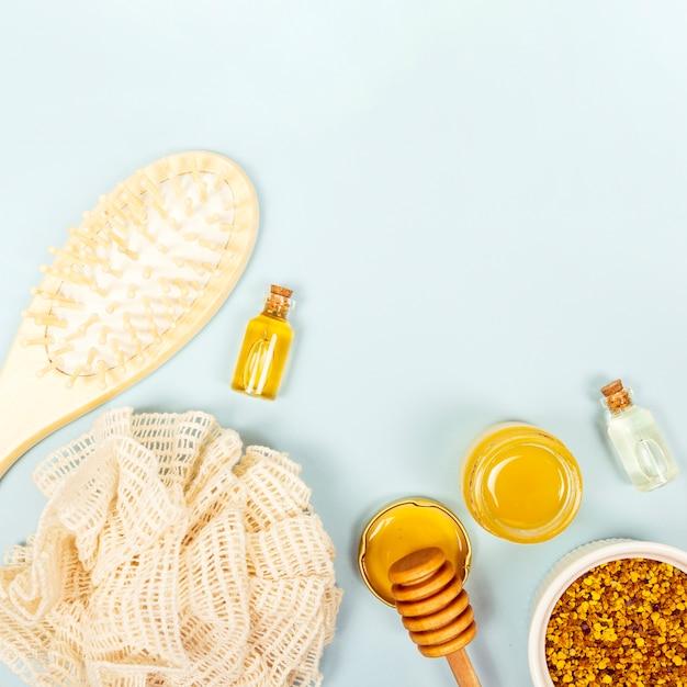 Obenliegende ansicht der bürste; flasche mit ätherischem öl; honigglas; bienenpollen und luffa Kostenlose Fotos