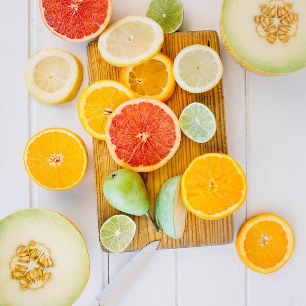 Obenliegende ansicht der halbierten moschusmelone mit birne und geschnittenen zitrusfrüchten auf hackendem brett Kostenlose Fotos