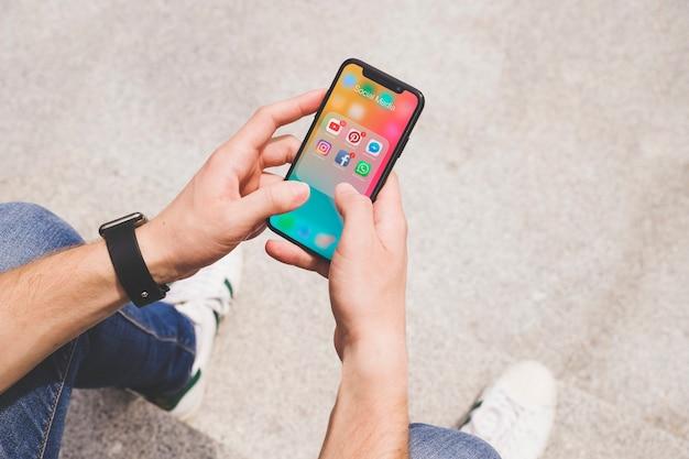 Obenliegende ansicht der hand des mannes unter verwendung der social media-app auf mobile Kostenlose Fotos