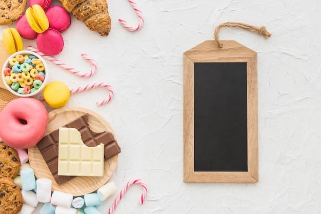 Obenliegende ansicht der hölzernen schiefermarke und der süßen nahrungsmittel auf weißem hintergrund Kostenlose Fotos