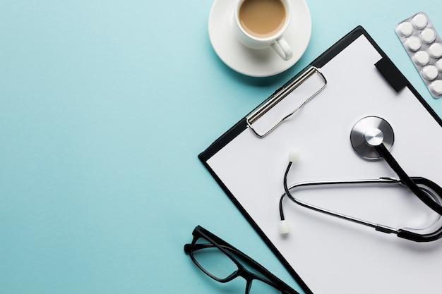 Obenliegende ansicht der kaffeetasse und der ausrüstung doktors auf blauer oberfläche Kostenlose Fotos