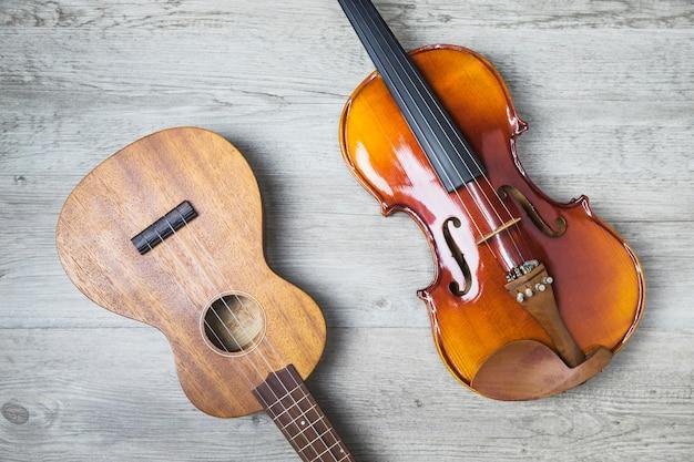 Obenliegende ansicht der klassischen gitarre und der violine auf hölzernem hintergrund Kostenlose Fotos