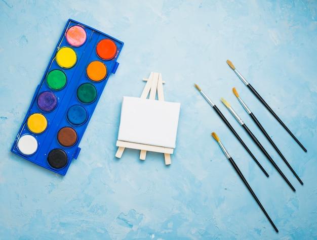 Obenliegende ansicht der malereiausrüstung auf blauem hintergrund Kostenlose Fotos
