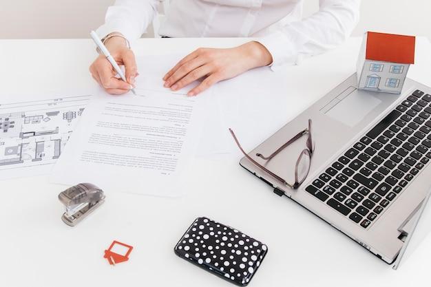 Obenliegende ansicht der menschlichen hand unterzeichnung am offiziellen papier im büro setzend Kostenlose Fotos