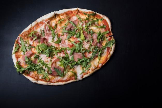 Obenliegende ansicht der pizza mit speck und arugula auf schwarzer küchenarbeitsplatte Kostenlose Fotos