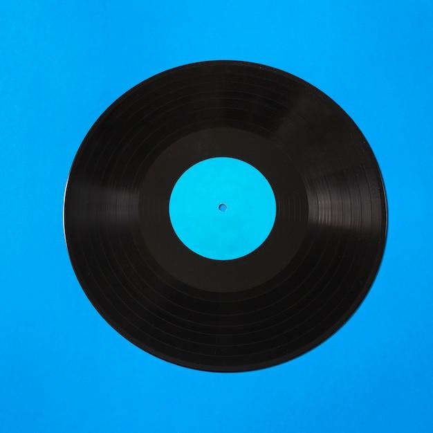 Obenliegende ansicht der vinylaufzeichnung auf blauem hintergrund Kostenlose Fotos