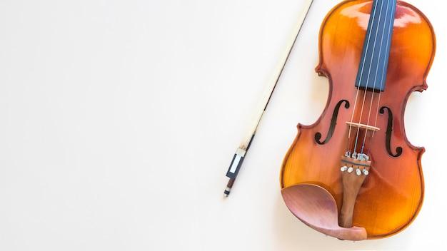 Obenliegende ansicht der violine mit bogen auf weißem hintergrund Kostenlose Fotos