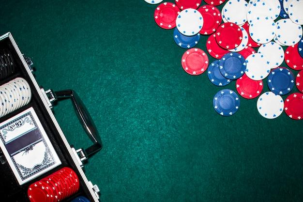 Obenliegende ansicht des aluminiumkoffers mit poker stellte auf schürhakentabelle ein Kostenlose Fotos