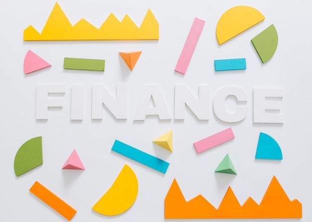 Obenliegende ansicht des finanzwortes mit buntem diagramm und geometrischer form Kostenlose Fotos