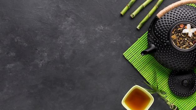 Obenliegende ansicht des getrockneten kraut- und bambusstocks mit teekanne auf schwarzem hintergrund Kostenlose Fotos