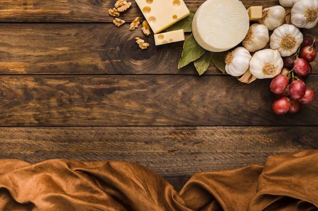 Obenliegende ansicht des käses und des bestandteils mit braunem stoff über verwittertem hölzernem schreibtisch Kostenlose Fotos