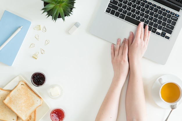 Obenliegende ansicht des laptops, des frischen sandwiches, der schale grünen tees und des handys auf weißer tischplattentabelle. frauengeschäft und frühstückskonzept, draufsicht und ebenenlage Premium Fotos