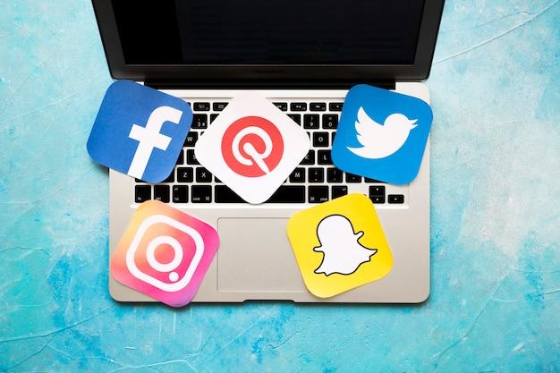 Obenliegende ansicht des laptops mit sozialmedizinikonen über dem blauen hintergrund Kostenlose Fotos